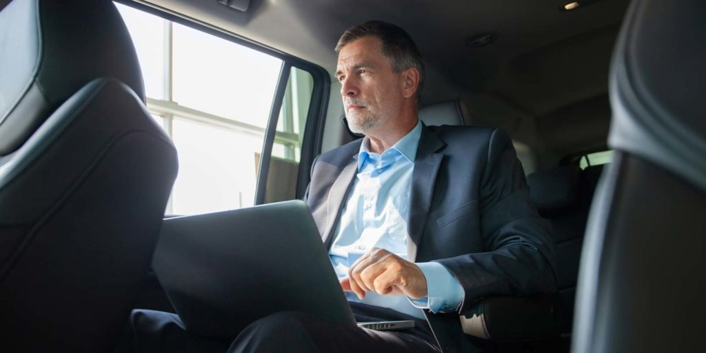 a-man-using-his-laptop-in-a-vehicle-with-good-amenities