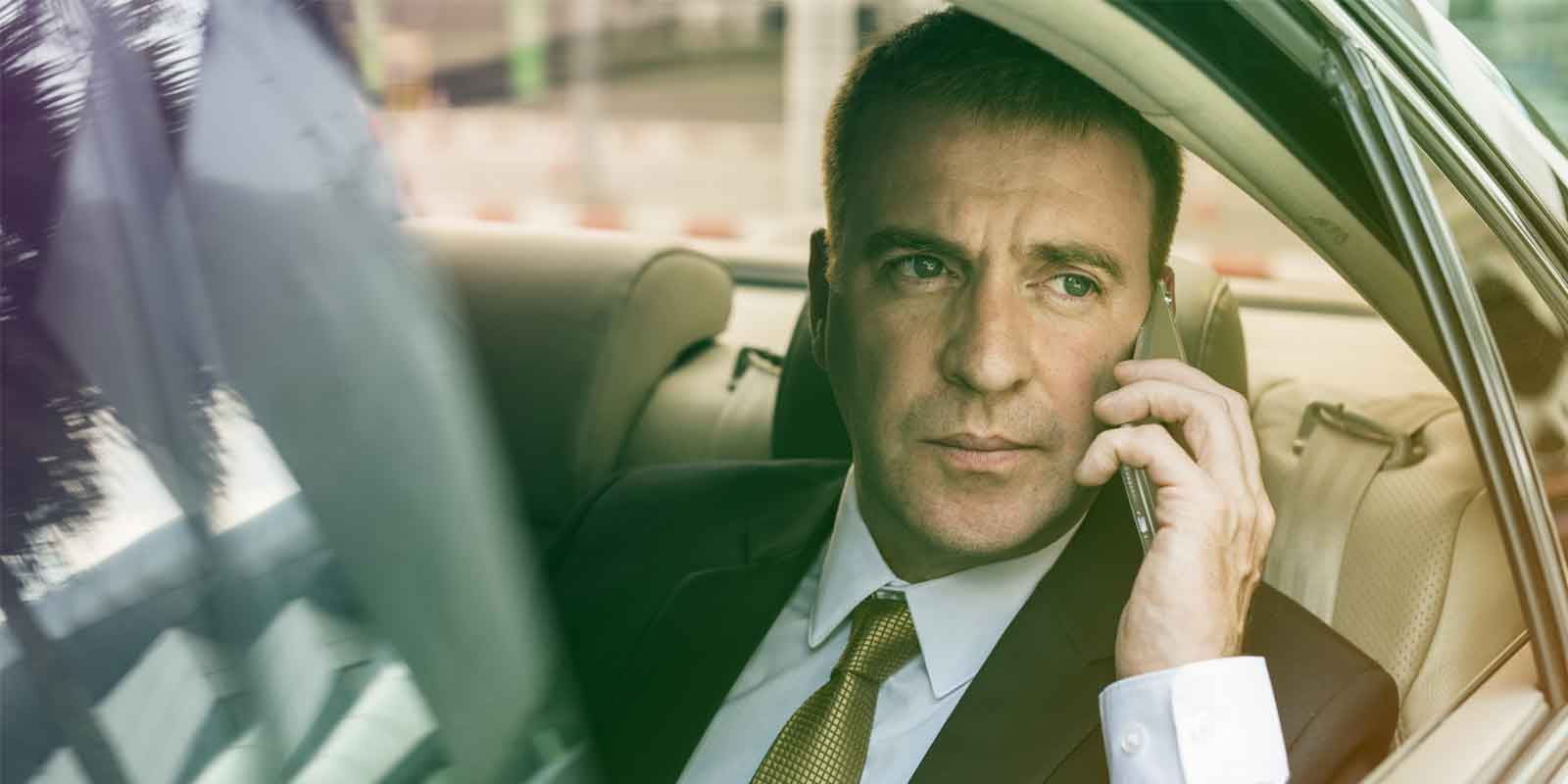 Man in a luxury sedan on the phone
