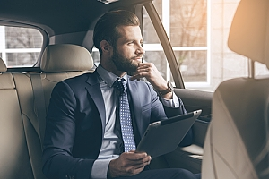 Businessman relaxing in back seat