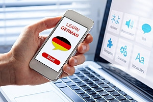 Hand holding phone with German language learning app and computer in background with language learning resource