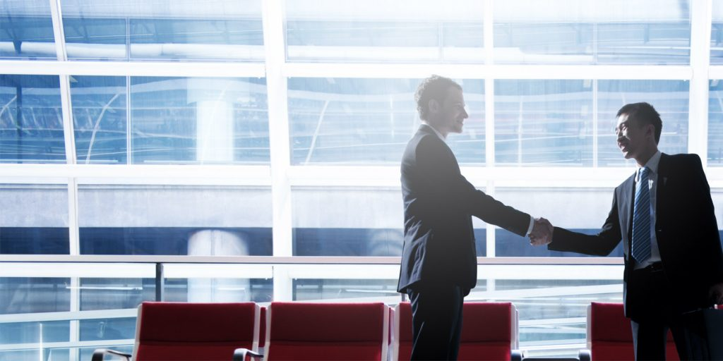 Businessmen meeting at international airport and shaking hands