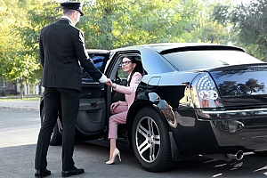 Business woman being helped out of a car