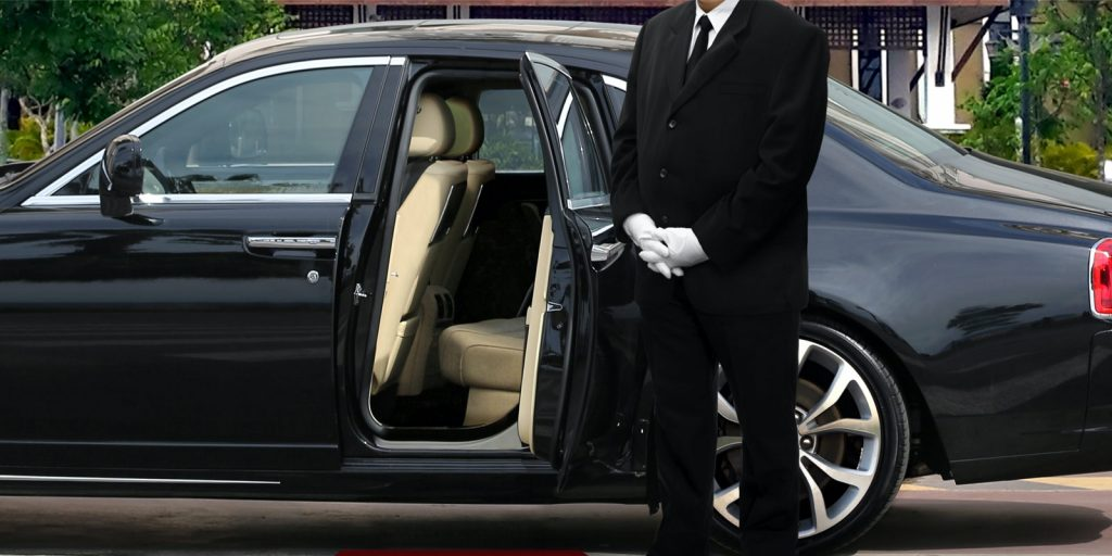 Professional driver waiting at open sedan door with red carpet